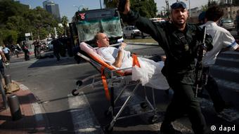 Israeli rescue workers and paramedics carry a wounded person from the site of a bombing in Tel Aviv, Israel, Wednesday, Nov. 21, 2012. A bomb ripped through an Israeli bus near the nation's military headquarters in Tel Aviv on Wednesday, wounding several people, Israeli officials said. The blast came amid a weeklong Israeli offensive against Palestinian militants in Gaza that has killed more than 130 Palestinians. (Foto:Oded Balilty/AP/dapd)