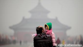 A young boy looks back while being carried by a man in front of the main hall of the 'Temple of Heaven' which is barely visible due to heavy smog in Beijing, China, 19 January 2012. (Photo: dpa)