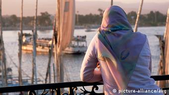 Back view of an Egyptian women looking at the Nile River Luxor - Luksor - El-Uksur (Ober- aegypten). - Frau an der Corniche el-Nil. - Foto, 2006.
