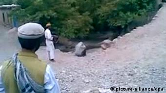 a woman crouches on ground , Taliban in front of her 