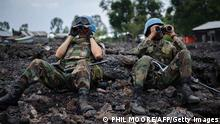 Uruguayan United Nations peacekeepers look through binoculars at M23 rebel positions on the outskirts of Goma, in eastern Democratic Republic of the Congo, on November 18, 2012. Government soldiers were fleeing the eastern DR Congo city of Goma in large numbers today as rebels advanced to the gates of the regional capital after fresh fighting erupted in the area last week, a UN source said. AFP PHOTO / PHIL MOORE (Photo credit should read PHIL MOORE/AFP/Getty Images)