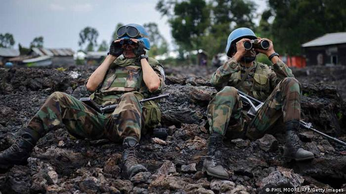 Two United Nations peacekeepers look through binoculars . AFP PHOTO / PHIL MOORE /AFP/Getty Images)