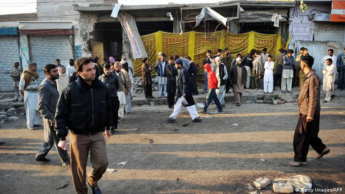 Local residents gather at the site of an overnight suicide bomb attack on minority Shiite Muslims procession in Rawalpindi on November 22, 2012