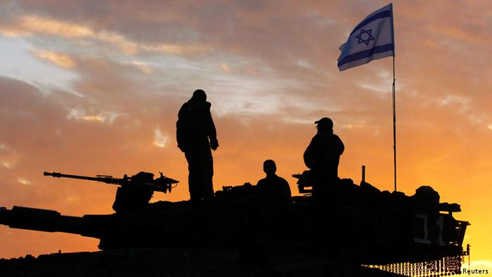 Israeli soldiers, atop a tank, prepare to leave their Gaza border position at sun rise REUTERS/Yannis Behrakis (ISRAEL - Tags: CONFLICT POLITICS)