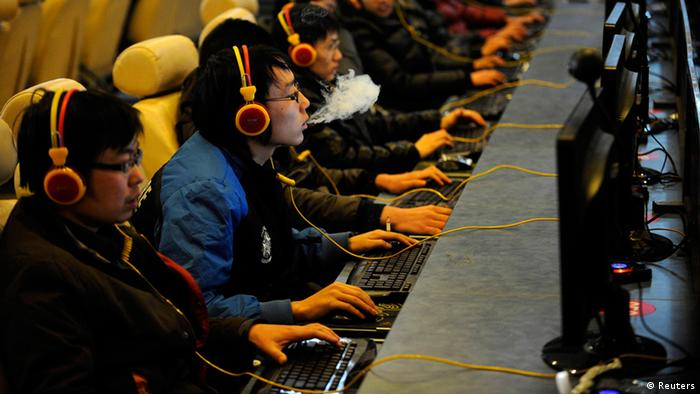 A man smokes while using a computer at an Internet cafe in Taiyuan, Shanxi province in this December 30, 2010 file photo. As China prepares for a generational power shift in the next two weeks, a similar shift is happening online that is testing the limits and displaying the evolution of China's legions of state-directed censors. Since its launch three years ago, Weibo, China's version of Twitter, has become the country's water cooler, a place where nearly 300 million Internet users opine on everything from Korean soap operas to China's latest political intrigue. REUTERS/Stringer/Files (CHINA - Tags: POLITICS SCIENCE TECHNOLOGY) CHINA OUT. NO COMMERCIAL OR EDITORIAL SALES IN CHINA