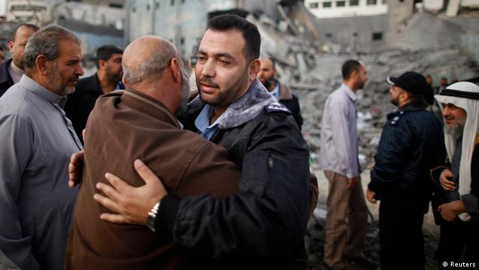 A Hamas police officer is hugged by a Palestinian man after they returned to their destroyed police headquarters in Gaza City November 22, 2012. A ceasefire between Israel and Gaza's Hamas rulers took hold on Thursday after eight days of conflict, although deep mistrust on both sides cast doubt on how long the Egyptian-sponsored deal can last. REUTERS/Suhaib Salem (GAZA - Tags: CONFLICT POLITICS)