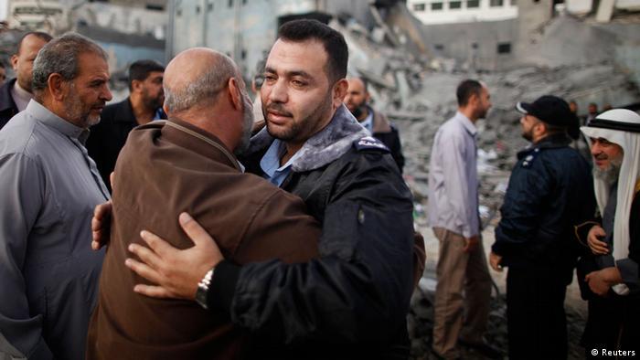 Ein Hamasoffizier umarmt einen Mann vor den trümmern des zerstörten Polizeiamtes in Gaza. (Foto: REUTERS)