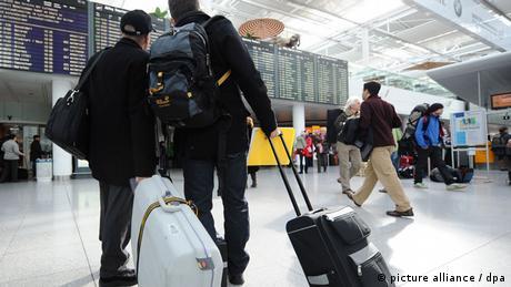 Люди с чемоданами стоят в аэропорту и смотрят на табло с информацией о рейсах