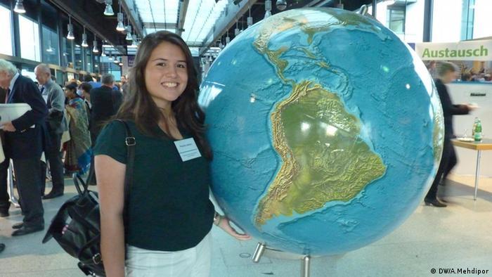 Priscillia Jenkins vor einer Weltkugel im Foyer der Deutschen Welle (Foto: DW / Anahita Mehdipor)
