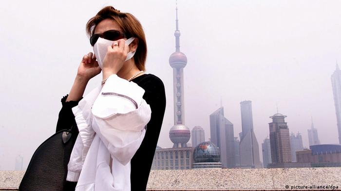 Tourist in Shanghai covers her mouth and nose with a surgical mask