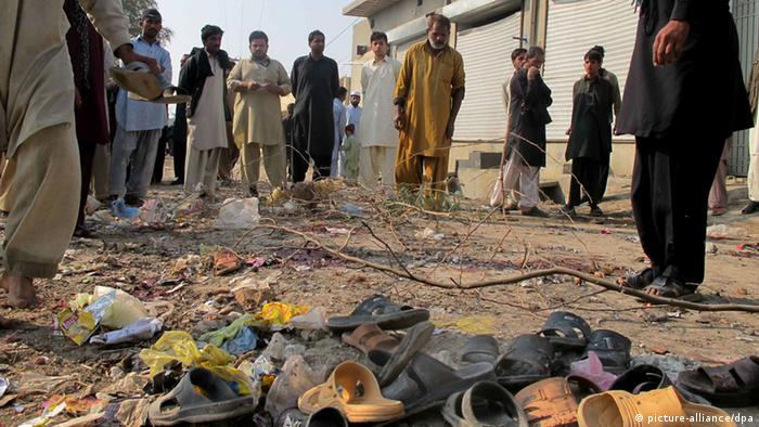 People survey the site of a remote control bomb blast targeting a Shi'ite Muslim mourning procession the Dera Ismail Khan Topanwala area of Khyber-Pakhtunkhwa provinc, Pakistan, 24 November 2012. At least seven civilians were killed on 24 November by a bomb at a procession of Muslim minority Shiites in Dera Ismail Khan, police said. The attack occurred during a commemoration of the Muharram festival in the Dera Ismail khan Topanwala area of Khyber-Pakhtunkhwa province. The bomb was hidden in a pile of rubbish along the procession route and detonated with a remote-controlled device, district police officer Sohail Khalid said EPA/SAOOD REHMAN