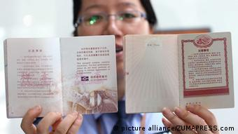 A policewoman shows the new biometric version (L) and the previous machine-readable version of the Chinese ordinary passport in Nantong, east China's Jiangsu Province, May 15, 2012