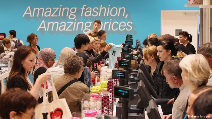 Shoppers at a row of checkouts in a fashion store