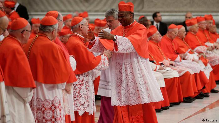 New Cardinal John Olorunfemi Onaiyekan of Nigeria (C) is congratulated by an unidentified cardinal during a consistory ceremony in Saint Peter's Basilica at the Vatican November 24, 2012. Pope Benedict XVI installed 6 new Roman Catholic cardinals from around the world on Saturday. REUTERS/Tony Gentile (VATICAN - Tags: RELIGION)