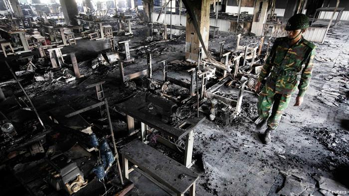 A soldier inspects the damage after a garment factory fire