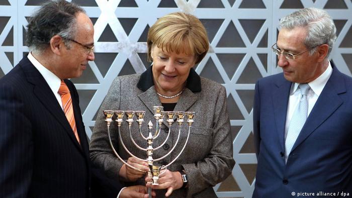 Merkel bekommt von Zentralrats-Präsident Graumann einen Chanukka-Leuchter überreicht (Foto: dpa)