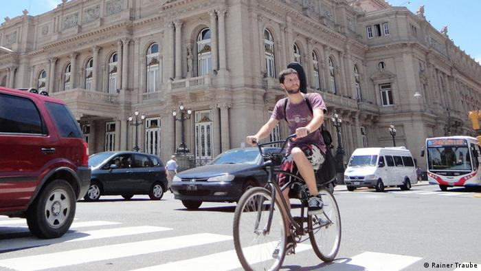 Young man riding bicycle outside with Teatro Colón in the background Copyright: Rainer Traube/DW