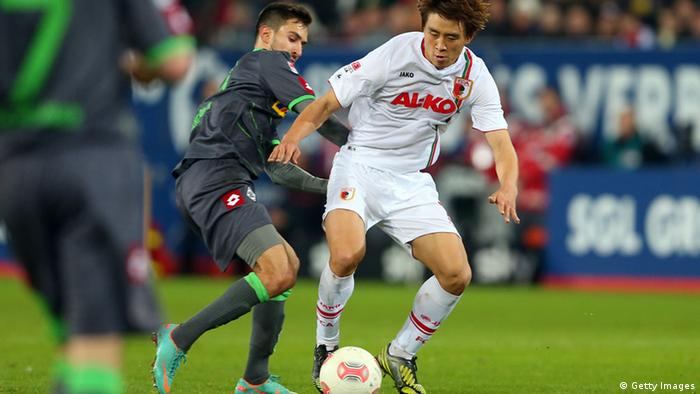 Ja-Cheol Koo (R) of Augsburg is challenged by Lukas Rupp of Gladbach during the Bundesliga match between FC Augsburg and VfL Borussia Moenchengladbach at SGL Arena on November 25, 2012 in Augsburg, Germany. (Photo by Alexander Hassenstein/Bongarts/Getty Images)