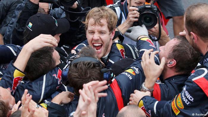 Red Bull Formula One driver Sebastian Vettel of Germany celebrates winning the world championship with his team after finishing sixth in the Brazilian F1 Grand Prix at Interlagos circuit in Sao Paulo November 25, 2012. Vettel became Formula One's youngest triple world champion at the age of 25 at the Brazilian Grand Prix on Sunday. REUTERS/Sergio Moraes (BRAZIL - Tags: SPORT MOTORSPORT SPORT MOTORSPORT F1)
