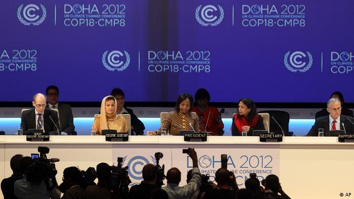 Organizers of the Doha climate conference speak into microphones before a blue background (Photo:Osama Faisal/AP/dapd)