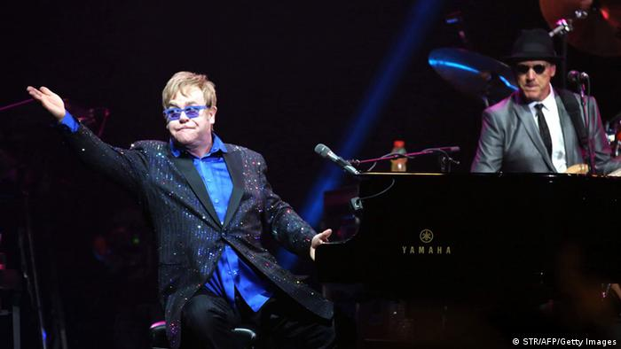 This picture taken on November 25, 2012 shows pop-rock balladeer Elton John (L) performing at his concert in Wukesong Stadium in Beijing. Elton dedicated his Beijing show to Chinese dissident Ai Weiwei -- a controversial move the artist said on November 26 was unlikely to make the nation's cultural minders happy. CHINA OUT AFP PHOTO (Photo credit should read STR/AFP/Getty Images)