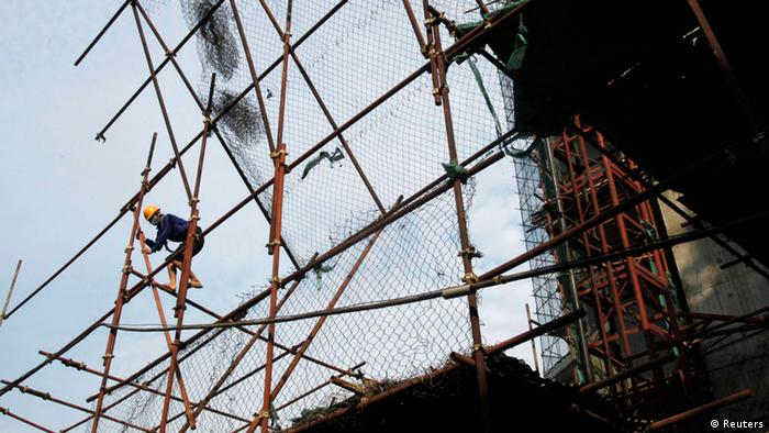 A worker climbs on a scaffolding at the construction site of a residential apartment in Hanoi REUTERS/Kham