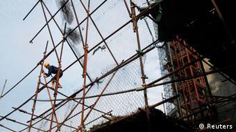 Ein Bauarbeiter klettert auf einem Gerüst in Hanoi in die Höhe (Foto: REUTERS/Kham).