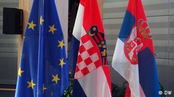 Two red, white and blue flags hang next to the blue and yellow flag of the EU (Photo: Marina Maksimovic/DW)