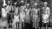 circa 1896: Slaves in chains, guarded by a native Askari, or soldier. (Photo by Hulton Archive/Getty Images)