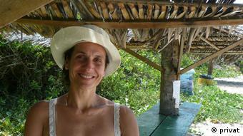 Claudia Marques Maximino mit Sonnenhut unter einem sonnenbeschienenen Strohdach. (Foto: privat)