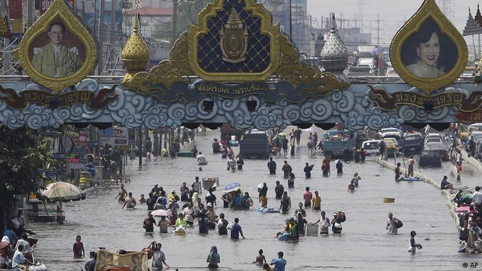 Dozens of people wade through water in an urban area