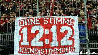 A supporters' banner reads 12:12 - without a voice there is no atmosphere