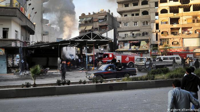 A handout picture released by the Syrian Arab News Agency (SANA), shows Syrian citizens inspecting the scene of a car bomb attack in Jaramana: Photo: EPA/SANA/ epa03488718
