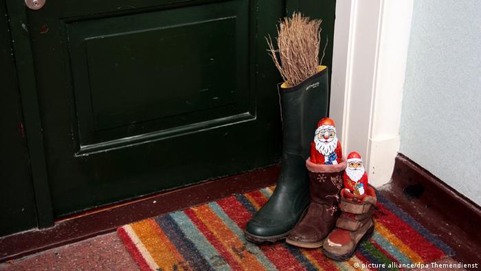 Vor einer Wohnungstür: drei Stiefel, gefüllt mit Süßigkeiten und einer Rute