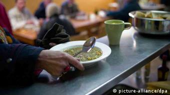 A person holding a bowl of soup Photo: Peter Steffen/dpa