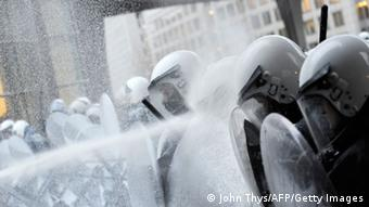 Demonstrators spray milk at police during a 2012 protest in Brussels against EU agricultural policy