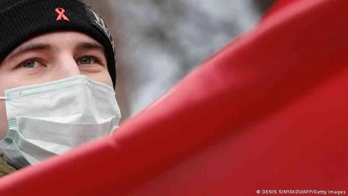 Человек, закрывающий лицо маской, на акции в поддержку прав ВИЧ-инфицированных в Москве