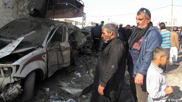 Residents gather at the site of a bomb attack in Hilla, 100 km (60 miles) south of Baghdad, November 29, 2012. Bombs in two majority Shi'ite Muslim cities in southern Iraq killed 28 people on Thursday, police and hospital sources said. REUTERS/Habib (IRAQ - Tags: CONFLICT CIVIL UNREST)