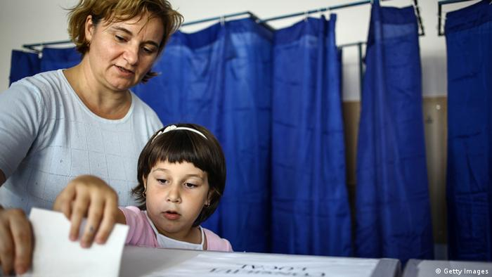 A girl helps a woman cast her vote on June 10, 2012, in Bucharest during local elections. More than 18 million Romanians were voting on June 10 to elect their mayors and local councillors in a country that is still looking for sustainable growth after a bite-the-bullet austerity package. AFP PHOTO / ANDREI PUNGOVSCHI (Photo credit should read ANDREI PUNGOVSCHI/AFP/GettyImages)