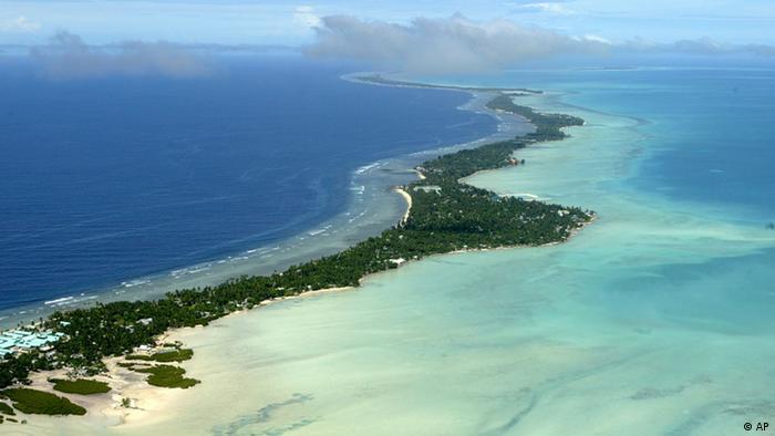 A long, thin, tree-topped island cuts a line through the blue Pacific ocean
