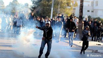 A protester throws a tear gas canister back at police during clashes in Siliana November 29, 2012. At least 200 people were injured when Tunisians demanding jobs clashed with police on Tuesday and Wednesday in the city of Siliana in a region on the edge of the Sahara desert that has long complained of economic deprivation