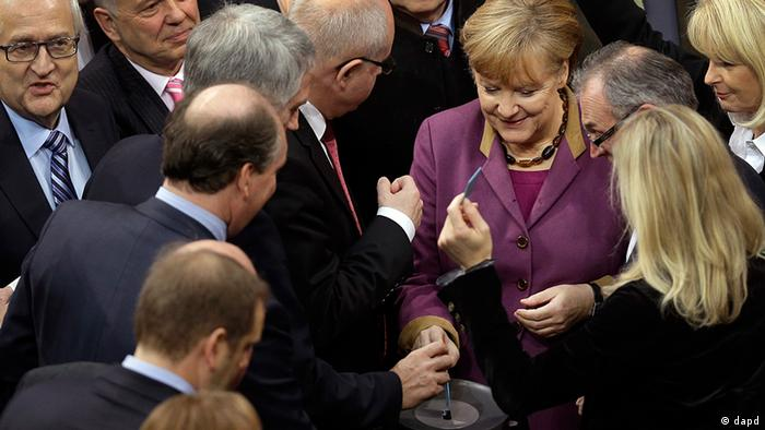 German Chancellor Angela Merkel casts her vote at f the German federal parliament, Bundestag, in Berlin, Germany, Friday, Nov. 30, 2012.The German Parliament has given its overwhelming backing to a deal aimed at trimming Greece's debt load and keeping the country financially afloat. Lawmakers voted 473-100 on Friday to back the complex deal reached by European finance ministers earlier this week..The agreement paves the way for Greece to receive 44 billion euro (US $57 billion) in critical rescue loans, without which the country would face bankruptcy and a possible exit from the euro. (Foto:Michael Sohn/AP/dapd)