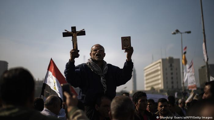 An Egyptian man holding a copy of the Koran and a cross in a crowd of people