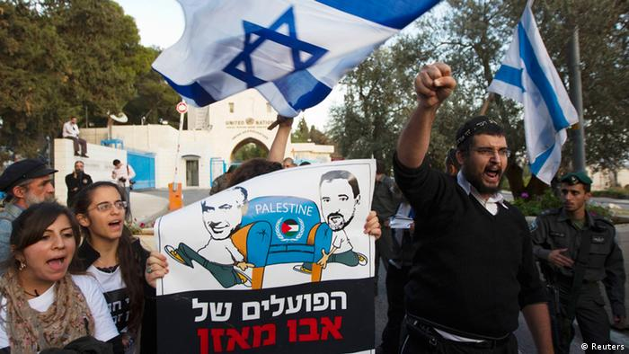 Israeli ultranationalist right-wing protesters hold a placard depicting Prime Minister Benjamin Netanyahu (L) and Foreign Minister Avigdor Lieberman during a demonstration against the Palestinian Authority's efforts to secure a diplomatic upgrade at the United Nations, outside the U.N. offices in the West Bank village of Jabel Mukaber, near Jerusalem November 29, 2012. (Photo via Reuters)