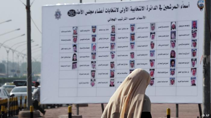 A Kuwaiti woman walks past a board with the names and photos candidates. (photo: Gustavo Ferrari/AP/dapd)
