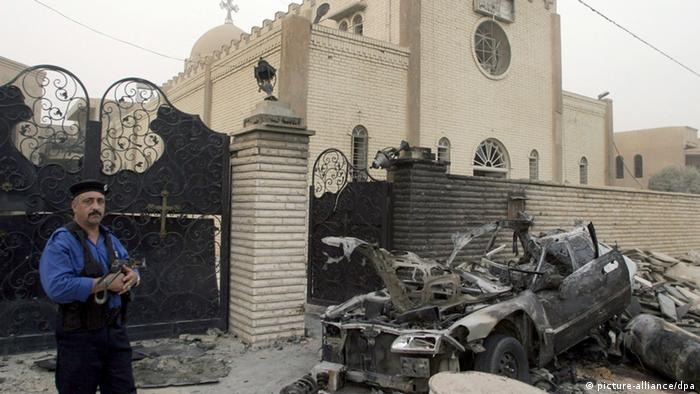 An Iraqi policeman stands guard at the site of a car bomb attack in front of a Christian church in Palestine Street, Baghdad, Iraq on 13 July 2009 (Photo: SHEHAB AHMED EPA)