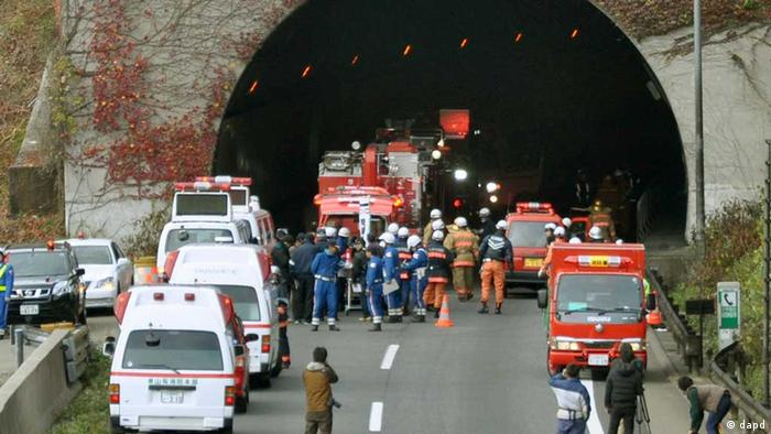 Police officers and firefighters gather at the exit of the Sasago Tunnel on the Chuo Expressway in Otsuki, Yamanashi Prefecture, central Japan, Sunday morning, Dec. 2, 2012.