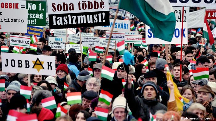 Protesters wave Hungarian national flags and hold placards, one reading Never again fascism (C-L), during a protest in front of the Parliament building in Budapest, Hungary, 02 December 2012.