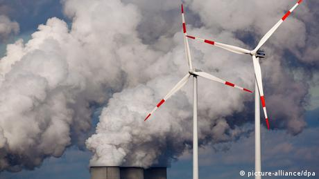 Two wind turbines against a backdrop of plumes of smoke billowing from factory chimneys