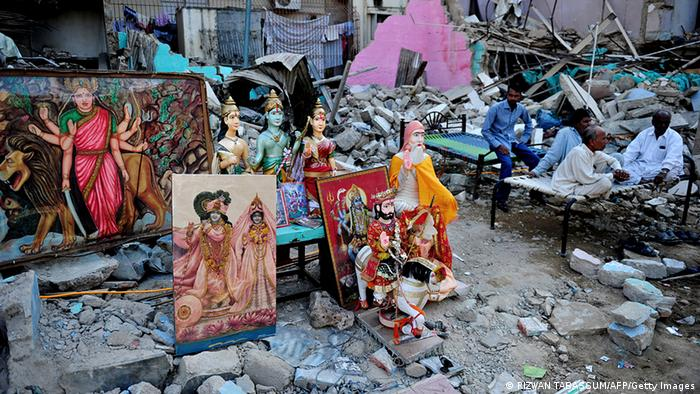 Pakistani Hindus sit next to a demolished Hindu temple in Karachi on December 2, 2012. Authorities have demolished a 50-year-old Hindu temple in southern Pakistani city of Karachi despite a stay order from a court sparking protest by the minority community, officials said (Photo: RIZWAN TABASSUM/AFP/Getty Images)